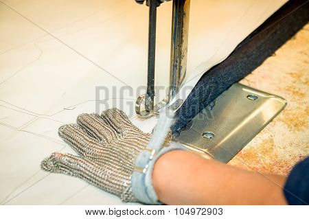 Hands wearing protection gloves using industrial machine for cutting carpets, textiles and other hea