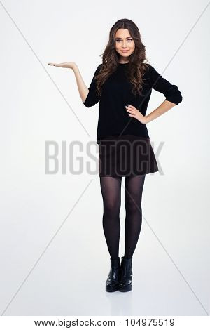 Full length portrait of a happy girl holding copyspace on the palm isolated on a white background
