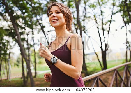 Happy Beautiful Girl Athlete Running In Park With Smart Watch On Hand