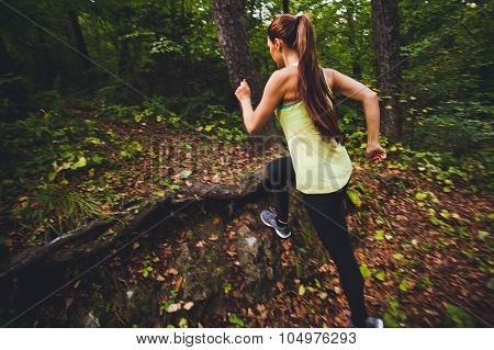 Attractive Young Woman Athlete Running In Forest