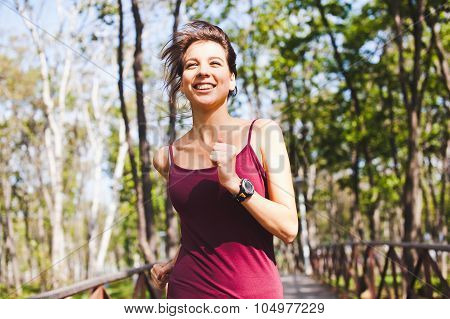 Beautiful Girl athlete Running In Park With Smart Watch On Hand
