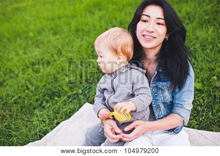 Beautiful Asian Mother With Her Blond Son Relaxing Outdoors. Unusual Appearance, Diversity Concept