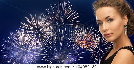 people, holidays and glamour concept - beautiful woman wearing earrings over firework on dark blue background