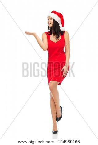 people, holidays, christmas and advertisement concept - beautiful sexy woman in santa hat and red dress showing something on empty hands