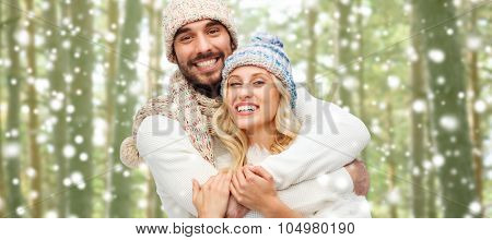 winter, fashion, couple, christmas and people concept - smiling man and woman in hats and scarf hugging over snowflakes and forest background