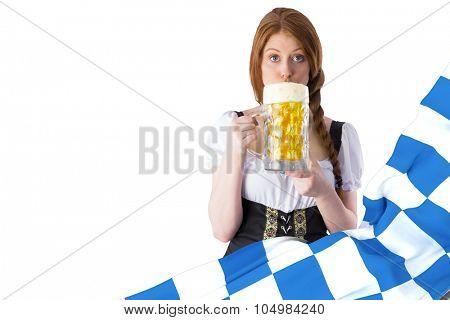 Oktoberfest girl drinking jug of beer against blue and white flag