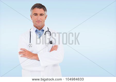 Serious doctor looking at camera against blue vignette background