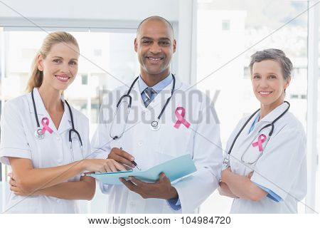 Pink breast cancer awareness ribbon against team of doctors working together on patients file