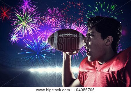 Aggressive sportsman with ball against fireworks exploding over football stadium