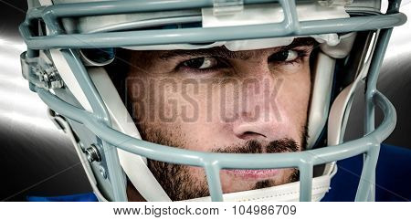 Close-up portrait of stern American football player against spotlight