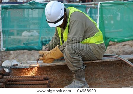 Construction workers cutting metal using blowtorch at the construction site