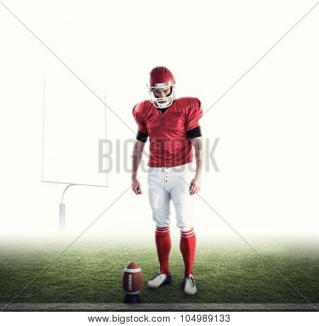 Portrait of american football player against american football posts