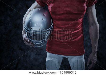 American football player holding helmet aside against dark background
