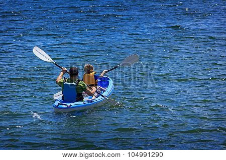 Happy little boy with his father kayaking at ocean