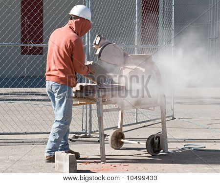 Worker Cutting Cement Block