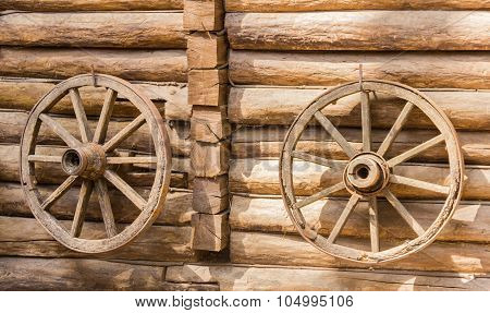 Two Old Cartwheel On A Wooden Wall