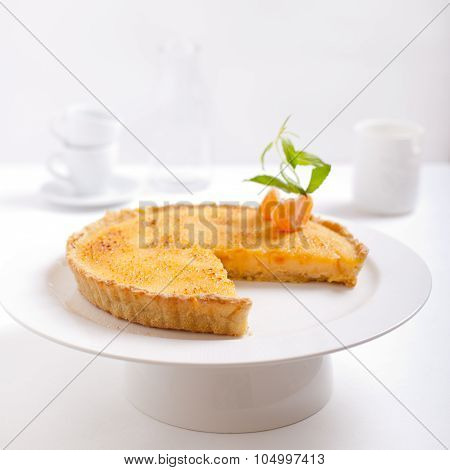 Tangerine creme brulee tart on a white background