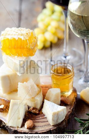 Cheese plate with honey, grape, wine in glasses