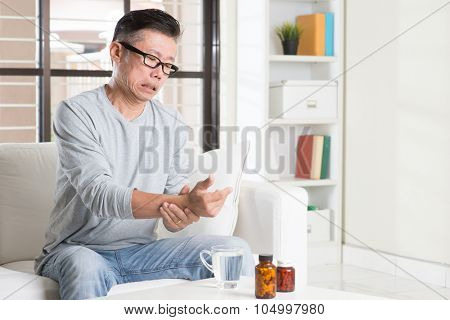 Portrait of casual 50s mature Asian man wrist pain, pressing on wrist with painful expression, sitting on sofa at home, medicines and water on table.