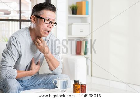 Casual 50s mature Asian man sore throat with painful face expression, hand on neck clearing throat, indoor home living lifestyle.