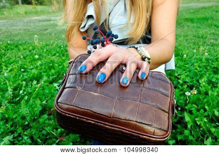 Woman Fingers With Blue Manicure On Clutch With Green Grass Background