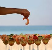 image of beach party  - woman is having shrimp cocktail on the beach - JPG