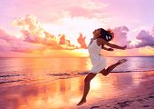 Happy beautiful free woman running on the beach at sunset jumping playful having fun in serene pictu poster