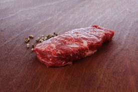 image of peppercorns  - fresh raw beef meat steak with white and green peppercorn spice on walnut table - JPG