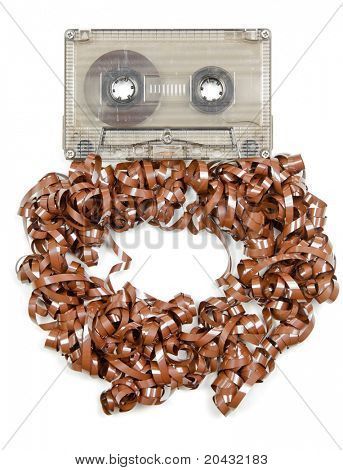 Vintage transparent Compact Cassette with pulled out tape on white background