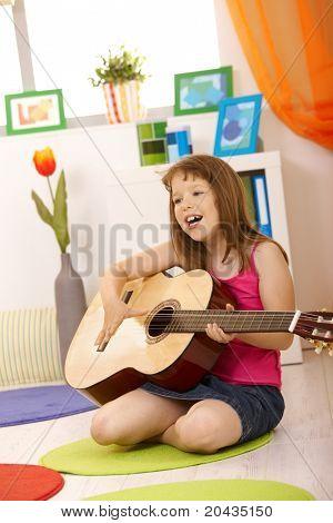 Porträt von Schülerin mit Gitarre, Gesang, sitzen auf dem Boden des Wohnzimmers.?