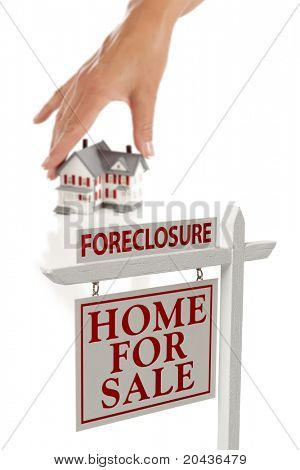 Woman's Hand Choosing House with Foreclosure Home For Sale Real Estate Sign in Front Isolated on White.