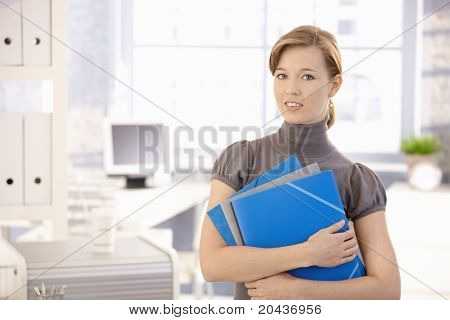 Portrait of young woman in office, holding file folders. Looking at camera, smiling.?