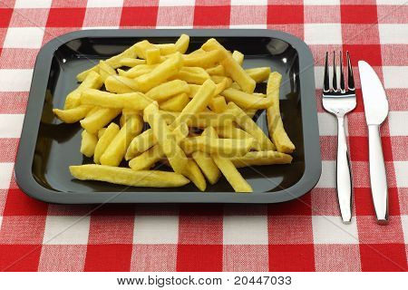 Freshly fried French fries on a plate  with cutlery