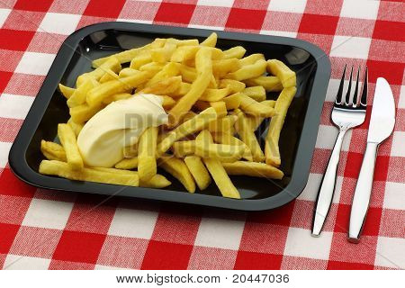 Freshly fried French fries with mayonnaise on a plate  with cutlery