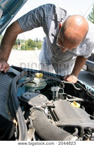 Businessman Checking The Engine Of A Car
