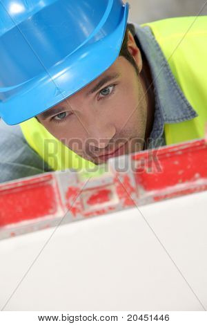 Worker using level on building site