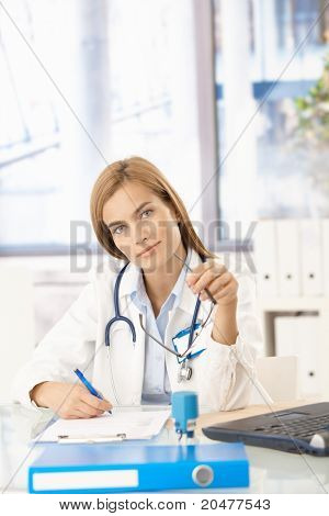 Young attractive female doctor working in office, sitting at desk, writing.?