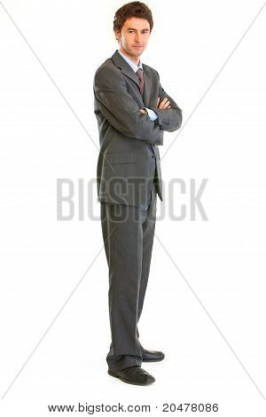 Full length portrait of serious businessman with crossed arms on chest isolated on white