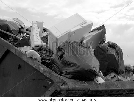 Black and white image of filled waste skip