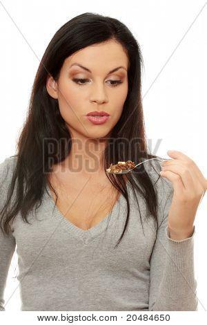 Junge schöne caucasian Frau schockiert während des Essens eines Kuchens - Löffel biegen - zuviel Kalorien Conce