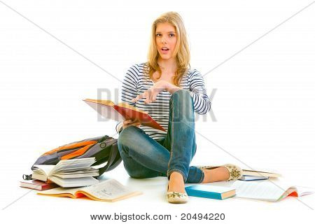 Shocked teen girl sitting on floor with schoolbag and pointing finger in open schoolbook isolated