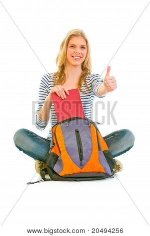 Sitting on floor smiling girl geting book from schoolbag and showing thumbs up gesture isolated