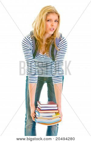 Shocked teen girl holding heavy pile of books in hands isolated on white