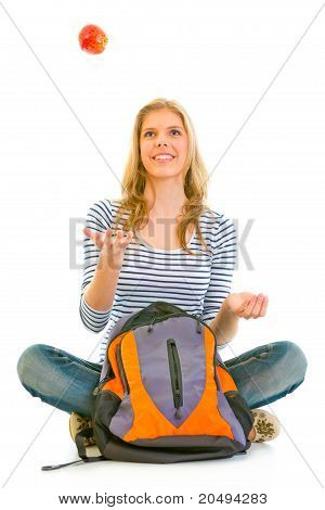 Smiling teengirl sitting on floor with schoolbag and throwing apple up isolated on white