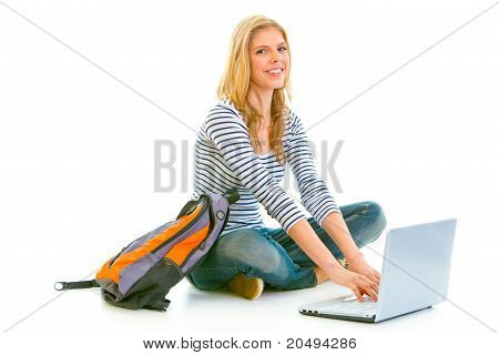 Smiling teengirl sitting on floor with schoolbag and using laptop isolated on white