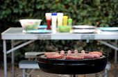 Sausages And Burgers Sizzling On A Barbecue, With A Camping Table In The Blurred Out Of Focus Backgr poster