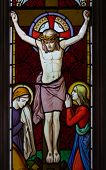 stock photo of inri  - detail of victorian stained glass church window in Fringford depicting Jesus nailed to the cross with St - JPG