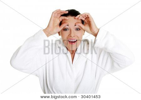 Beautiful caucasian woman checking her wrinkles on her forehead, isolated on white background