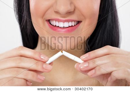 Young woman breaking cigarette, concept-  quitting smoking