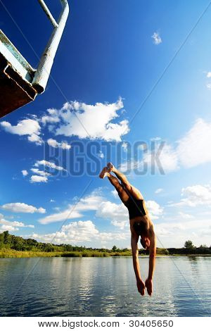 Young man jumping into a lake
